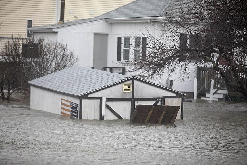 A shed and home in Quincy, Massachusetts, are inundated as a north-easter hits the east coast on Friday, bringing coastal flooding, heavy snow and strong winds to the area.
