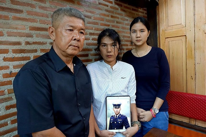 Mrs Sukanya Tanyakan holding a photo of her late son Pakapong Tanyakan in cadet uniform, with husband Pichet Tanyakan and daughter Supicha Tanyakan. Although heart failure was the official reason given for the boy's death while training at Thailand's