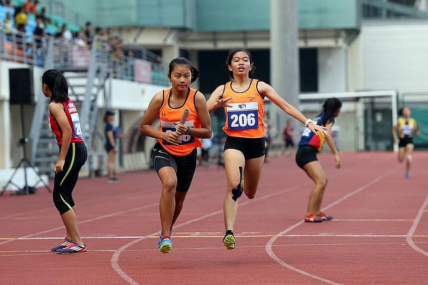 Singapore Sports School's Diane Pragasam passing the baton to team-mate Palada Tang in the A Division girls' 4x200m relay final yesterday. The team won the event and will compete in the 4x100m and 4x400m at Bishan Stadium today.