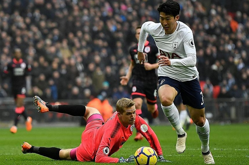 Tottenham forward Son Heung Min rounding Huddersfield Town goalkeeper Jonas Lossl before scoring the 27th-minute opener in their Premier League game at Wembley yesterday. The South Korean added a second in the 54th minute by heading in Harry Kane's c
