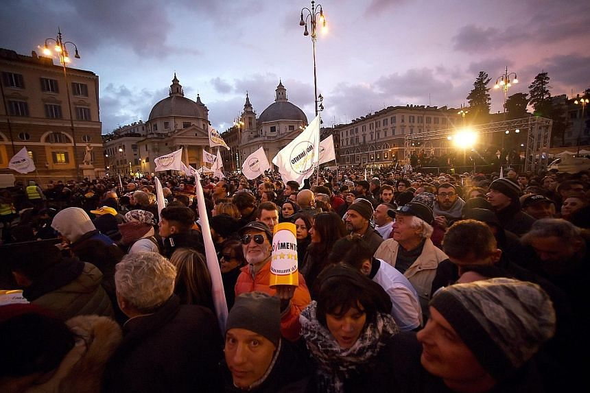 Supporters of the anti-establishment Five Star Movement gathering at the end of the last election campaign meeting by party leader Luigi Di Maio in Piazza del Popolo in Rome last Friday. Campaigning was not allowed yesterday, on the eve of the poll.