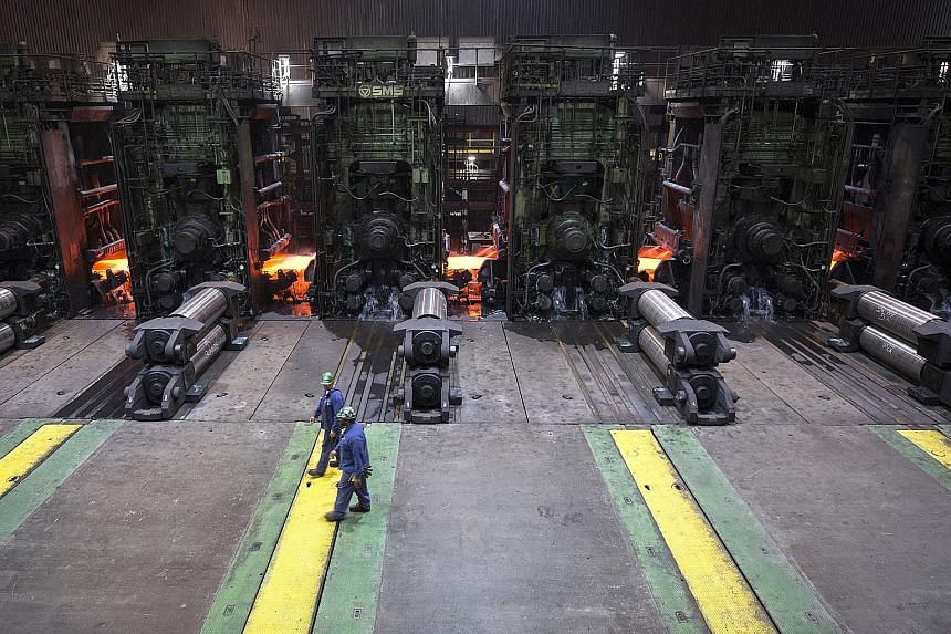 Workers at a South Carolina mill where sheets of hot steel are flattened into rolled steel. President Donald Trump is planning to impose tariffs of 25 per cent on steel imports and 10 per cent on aluminium imports from all countries. The tariffs will