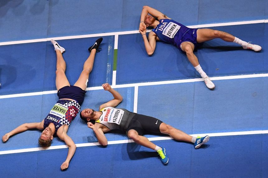 France's Kevin Mayer (left), Germany's Kai Kazmirek (centre) and US athlete Zach Ziemek collapse after the men's 1,000m heptathlon event.