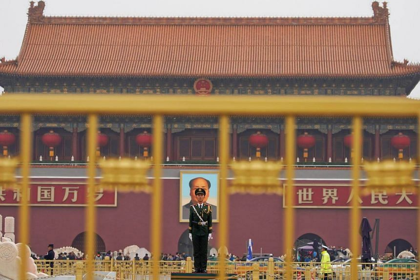 A paramilitary policeman stands guard before a portrait of late Chinese Chairman Mao Zedong at the Tiananmen gate in Beijing.