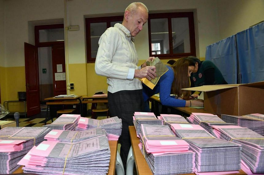 Polling station officials make final preparations ahead of the general elections, inside a polling station in Milan on March 3, 2018.