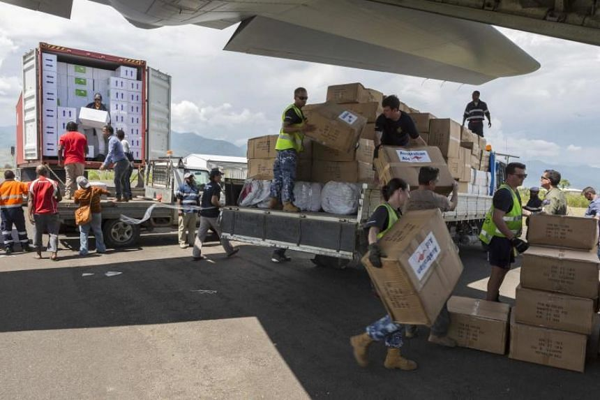 Royal Australian Air Force (RAAF) personnel along with Australian High Commission officials and Papua New Guinean locals unload humanitarian aid from trucks onto an RAAF C-130J aircraft in Lae, bound for earthquake-affected areas in the Papua New Gui