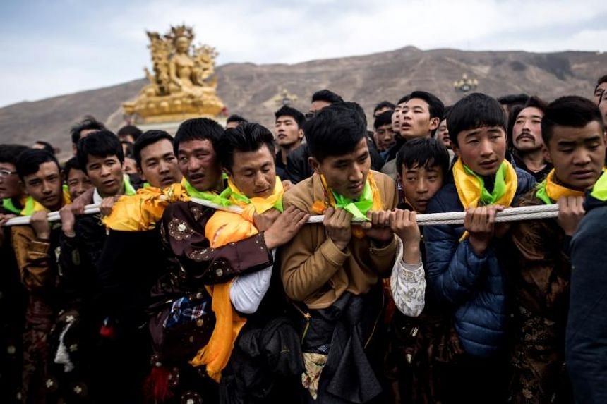 Tibetan Buddhist devotees pull a giant thangka during a ceremony for Monlam, otherwise known as the Great Prayer Festival of Losar, the Tibetan New Year, at the Rongwo Monastery, on the Qinghai-Tibet plateau.