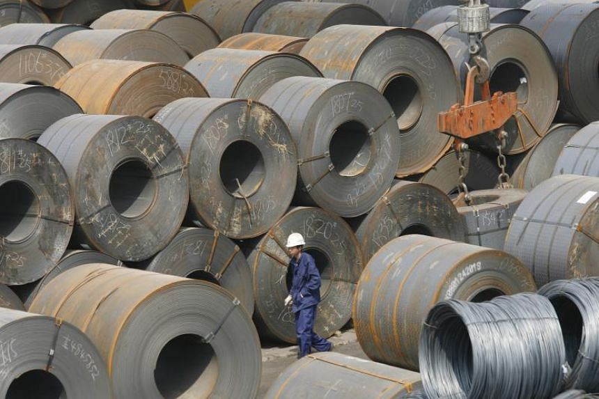 A Chinese worker is dwarfed by huge rolls of steel in a transhipment yard in northeast China's Shenyang.
