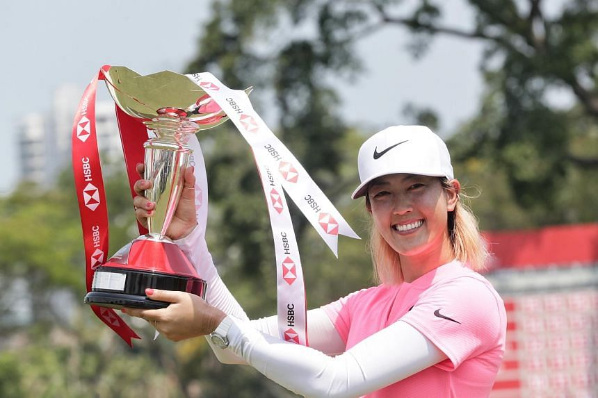 Golfer Michelle Wie lifting her trophy after winning the HSBC Women's World Championship, on March 4, 2018.
