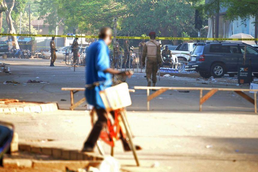 A cyclist watches military personnel outside the headquarters of the country's defence forces in Ouagadougou on March 3, 2018