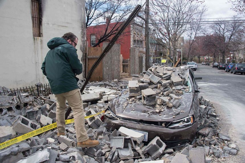 An insurance company employee checks the damage to a car after a partially burnt building collapsed due to strong winds.