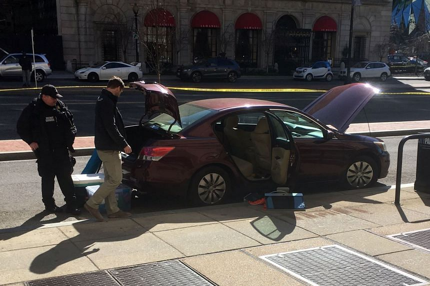 US Secret Service officers inspect a car reportedly belonging to the man who shot himself.