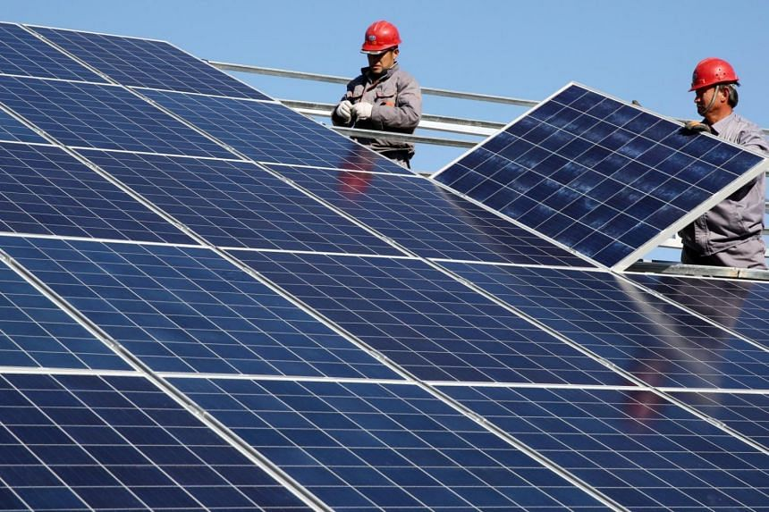 Workers installing solar panels at a residential home in a village in Dongying, Shandong province, China, on Nov 22, 2017.