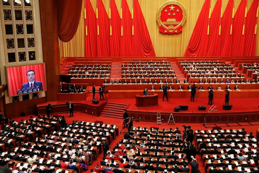 Chinese Premier Li Keqiang addresses delegates during the opening session of the National People's Congress at the Great Hall of the People in Beijing, on March 5, 2018.