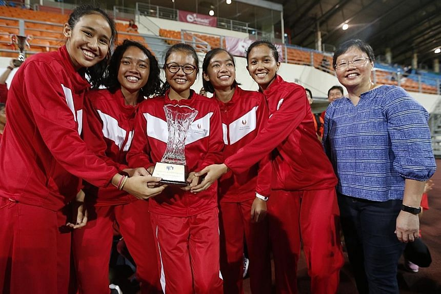 SSP's A Division girls' 4x100m quartet and ST sports editor Lee Yulin posing with the Tay Cheng Khoon Memorial Trophy.