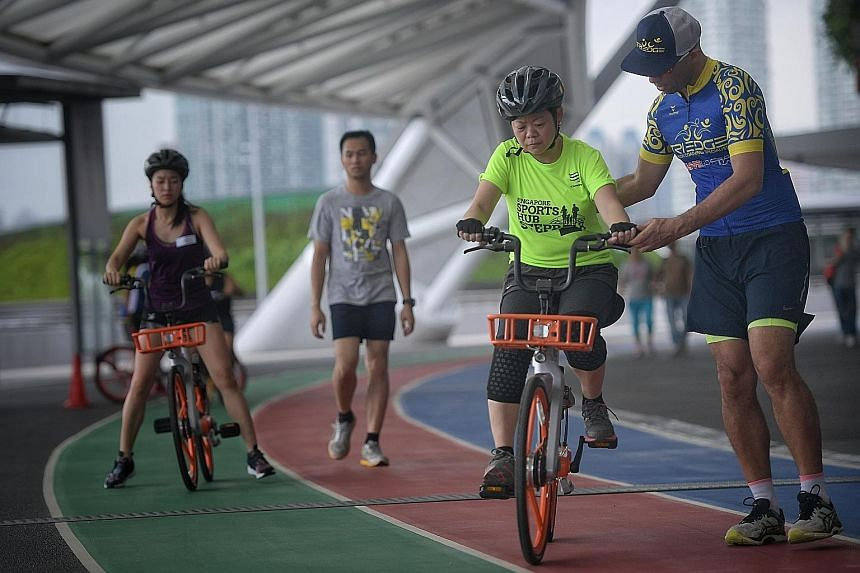 Instructors from Tri Edge helping people to learn how to cycle under the Project Training Wheels initiative on Saturday.