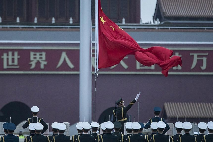 Members of the People's Liberation Army honour guard performing the daily flag-raising ceremony at Tiananmen Square in Beijing yesterday. The National People's Congress' annual session begins today and will last two weeks, longer than the traditional