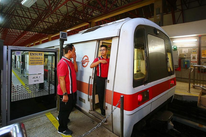"""SMRT train captain Mohamad Rezza Abdul Malek (right) taking over from a colleague during yesterday's trial. The 31-year-old, who recently welcomed a baby girl but came back on his day off to help out with the testing, said: """"Every day is a learning p"""