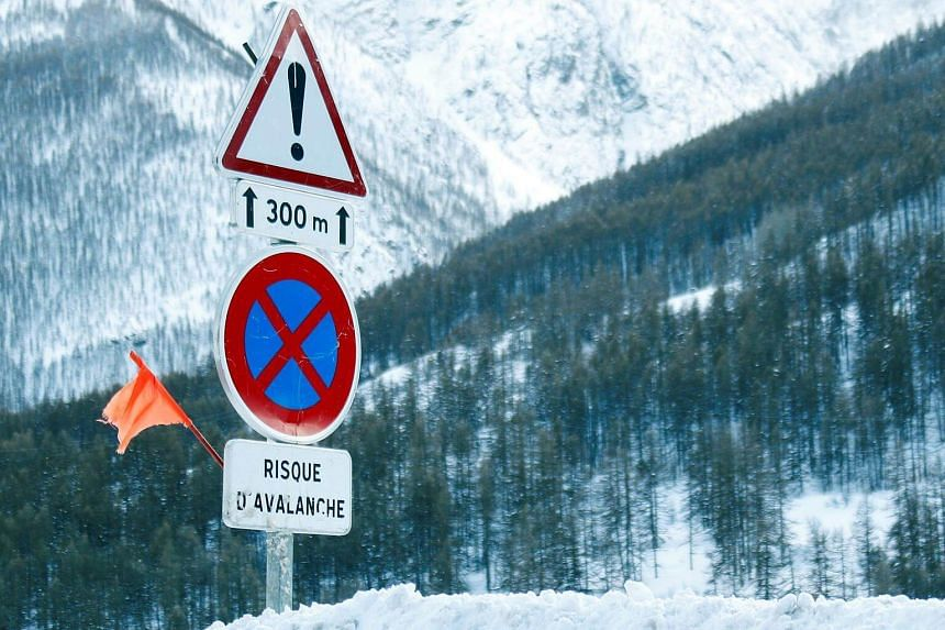 """A sign that reads """"avalanche risk"""" on a snow-covered road in Saint-Pancrace, France, on March 2, 2018."""