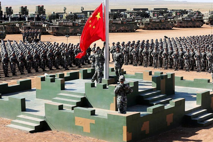 Soldiers of the People's Liberation Army raising the Chinese national flag during a parade at the Zhurihe military training base in Inner Mongolia on July 30, 2017.