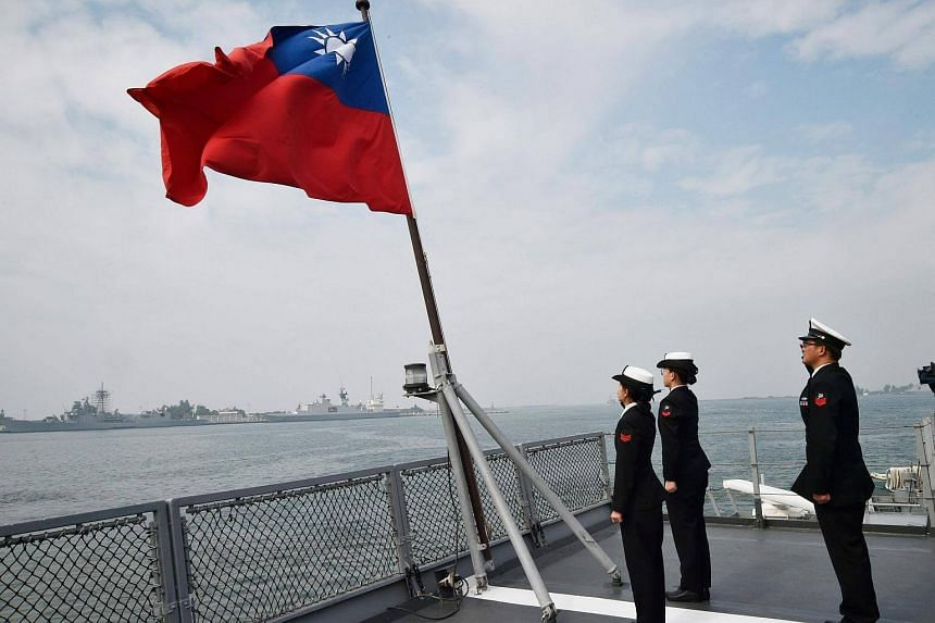 Taiwanese sailors saluting the island's flag on the deck of a supply ship after taking part in annual drills at the Tsoying naval base in Kaohsiung on Jan 31, 2018.