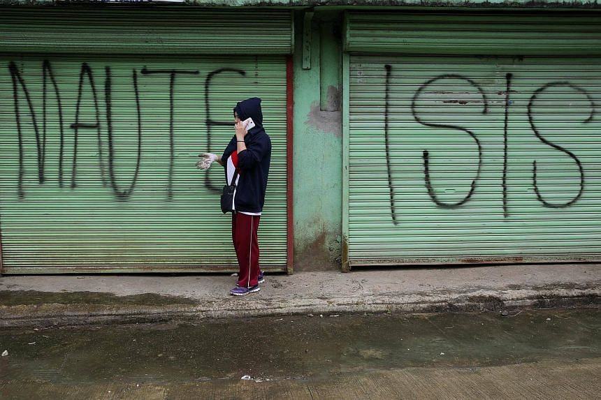 A local government worker in front of an establishment marked with graffiti inside the war-torn Marawi city, Philippines, on Oct 20, 2017.