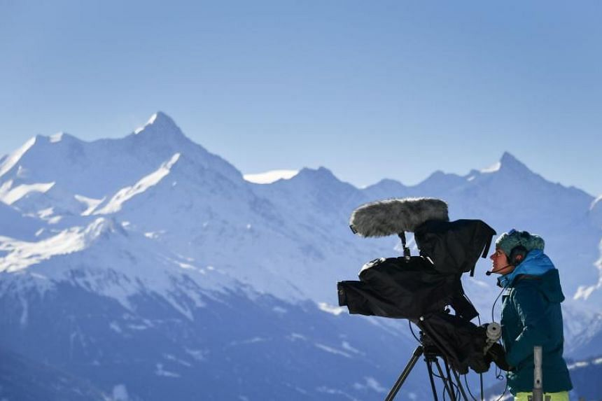 A cameraman of Swiss Broadcasting Corporation operates with the Swiss Alps in the background during a ski race in Crans-Montana on March 4, 2018.