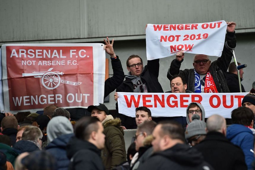 Arsenal supporters hold up anti-Wenger banners in the crowd after the English Premier League match between Brighton and Hove Albion and Arsenal at the American Express Community Stadium in Brighton on March 4, 2018.