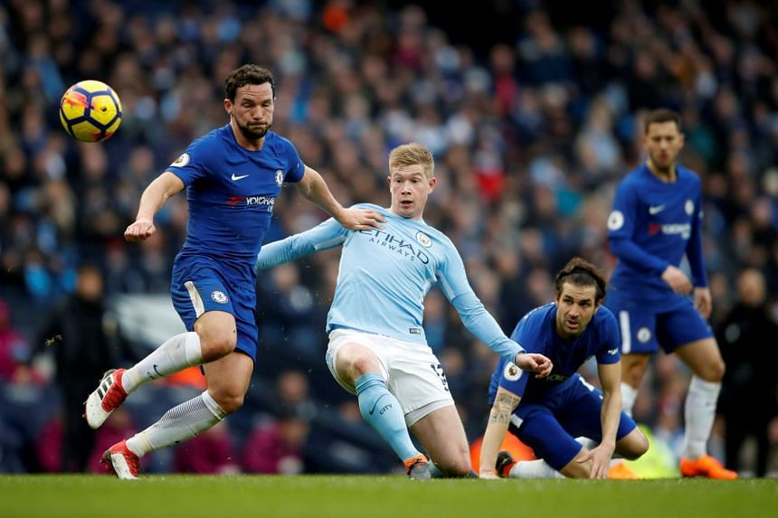 Manchester City' Kevin De Bruyne in action with Chelsea's Danny Drinkwater as Chelsea's Cesc Fabregas looks on during their English Premier League match at Etihad Stadium in Manchester on March 4, 2018.
