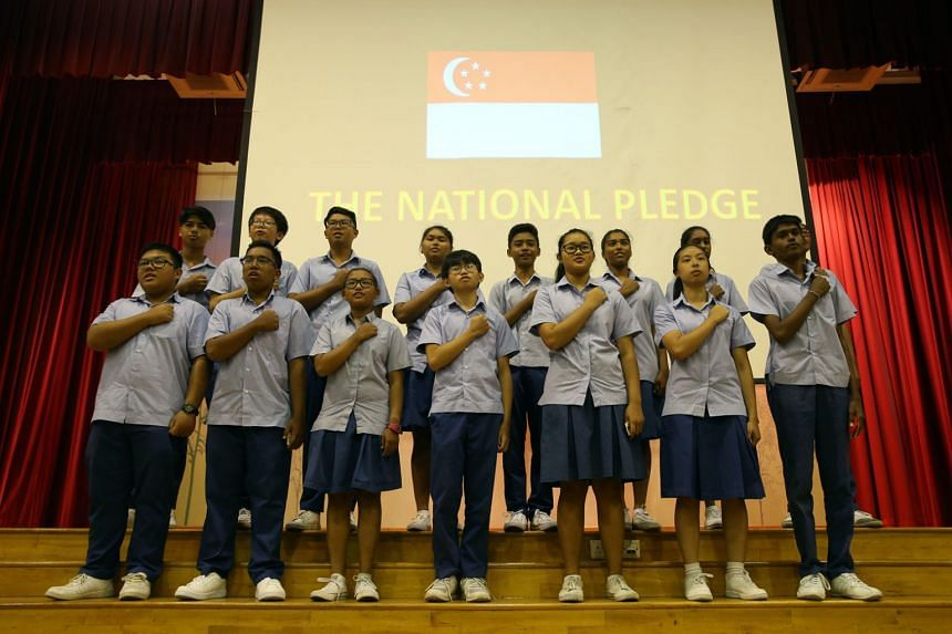 Ping Yi Secondary School students reciting the national pledge after receiving their identity cards in a ceremony at the school hall on March 5, 2018.