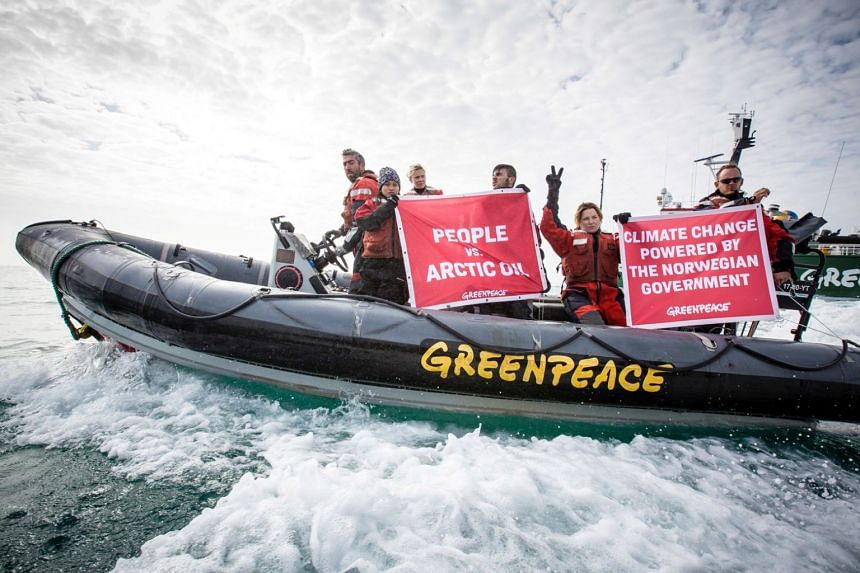 Greenpeace activists hold banners during a protest next to Statoil's Songa Enabler oil rig in the Barents sea, Norway, on July 21, 2017.