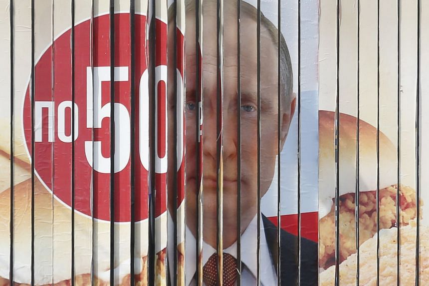 A multi-sided transformable board, which advertises the campaign of Russian President Vladimir Putin ahead of the upcoming presidential election, is on display in a street in Stavropol, Russia, March 5, 2018.