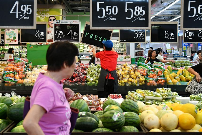 Customers browsing the fruits section of the FairPrice Xtra hypermarket in NEX shopping mall.
