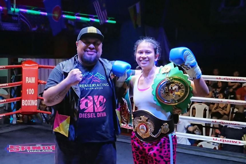 "Professional boxer Nurshahidah ""The Sniper"" Roslie celebrating with her trainer Arvind Lalwani after winning the Professional Boxing Association of Thailand's international featherweight title on Saturday night in Bangkok. She extended her winning st"
