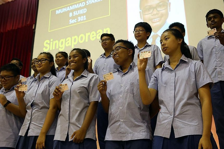 More than 70 Secondary 3 students from Ping Yi Secondary School receiving their NRICs at a presentation ceremony at their school yesterday. Before the ceremony, the students took part in a reflection session on what it means to be Singaporean.