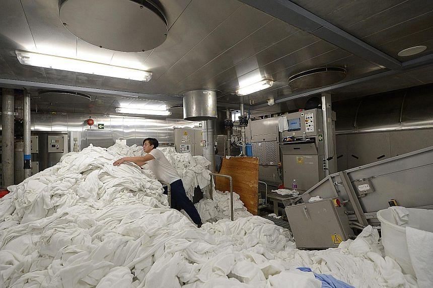 A worker tackles an enormous load in the laundry room, deep in the belly of the ship. The 17-strong crew are in charge of washing the cloths that cover everything from guest beds to the tables of restaurants. A cleaner using a jet spray to sanitise a