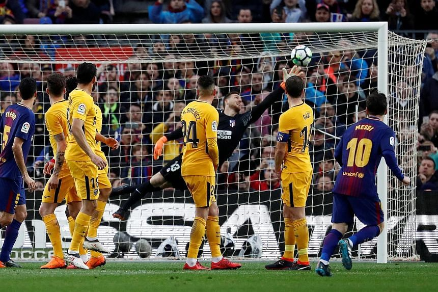 Atletico Madrid players can only watch as Lionel Messi's free kick is struck beyond the despairing dive of goalkeeper Jan Oblak. The goal separated Spain's top two sides, with Barcelona's lead at the top now eight points.