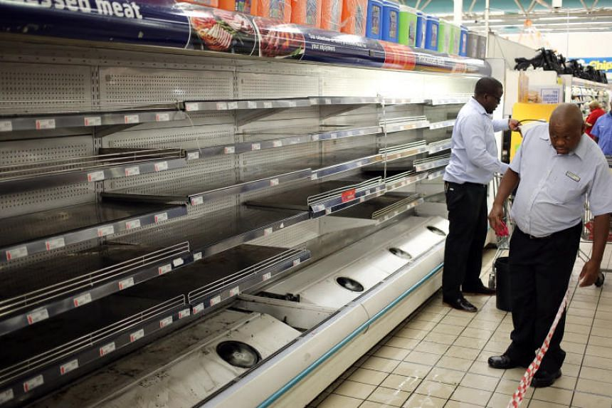 A worker looks at empty shelves after removing processed meat products at a Pick n Pay Store in Johannesburg, South Africa, on March 5, 2018.