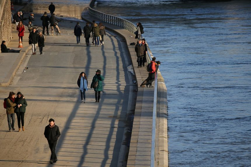 People walk along the banks of the Seine River in Paris on Feb 22, 2018.