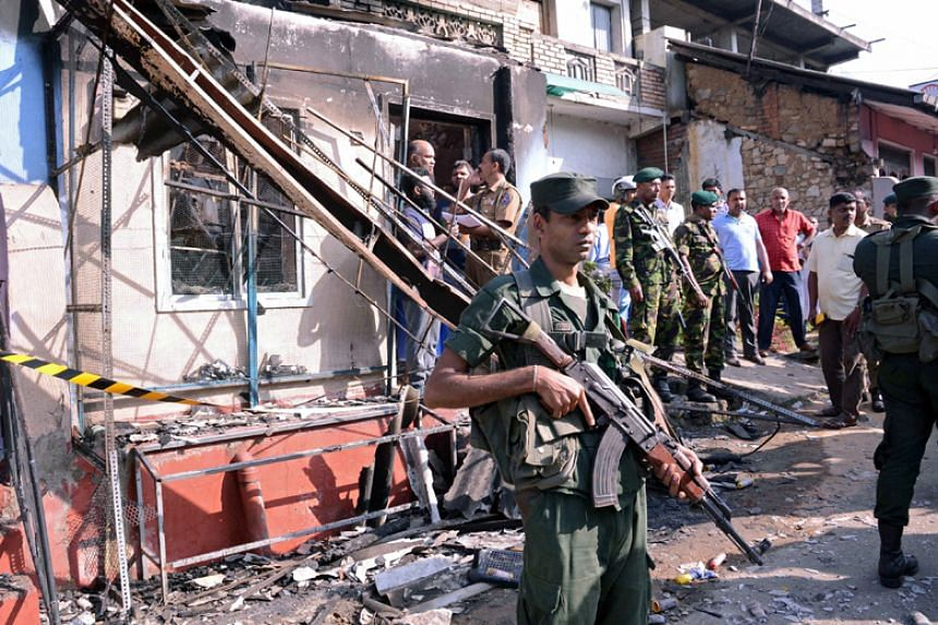Sri Lanka's army soldiers stand guard near a burnt house after a clash between two communities in Sri Lanka's central district of Kandy on March 6, 2018.