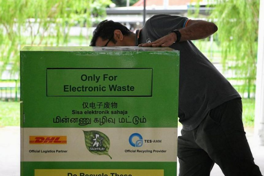 A man inspecting a recycling bin for electronic waste at the South West Community Development Council's annual trash-for-groceries recycling drive on Jan 14, 2018.