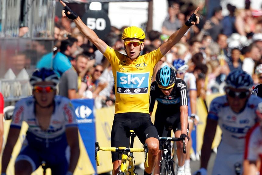 Sky Procycling rider and leader's yellow jersey Bradley Wiggins of Britain celebrates on the finish line after the final 20th stage of the 99th Tour de France cycling race between Rambouillet and Paris, France, on July 22, 2012.