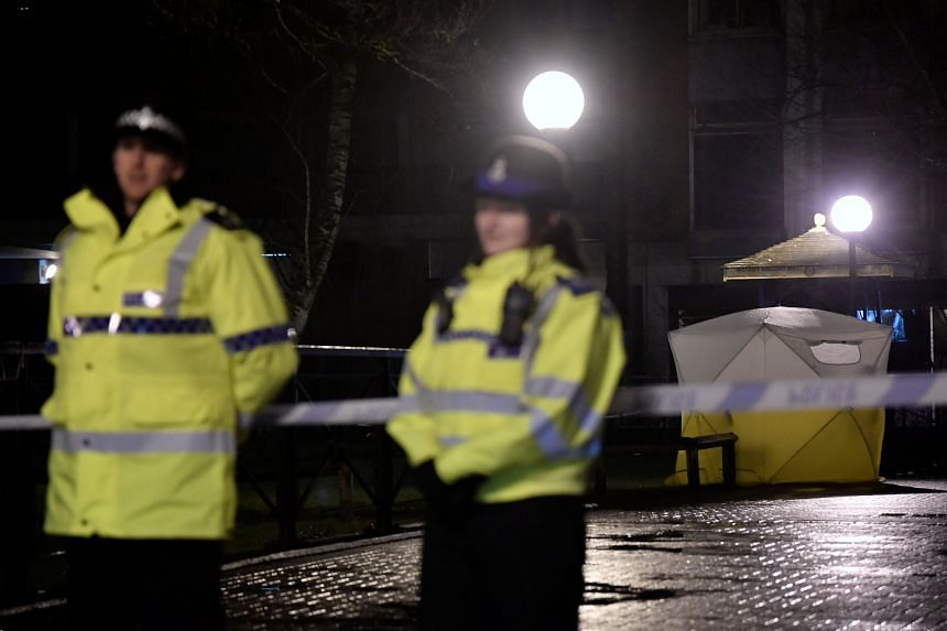 Police officers stand guard beside a cordoned-off area after Sergei Skripal became critically ill after exposure to an unidentified substance, in Salisbury, southern England, on March 5, 2018.