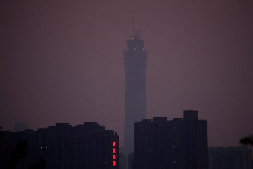 The construction site of China Zun, planned to be the tallest building in Beijing, is seen amid smog at sunset in Beijing, China on July 9, 2017.