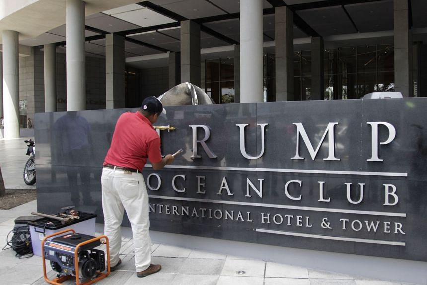 A worker removing the Trump sign outside the Trump Ocean Club International Hotel and Tower in Panama City on March 5, 2018.