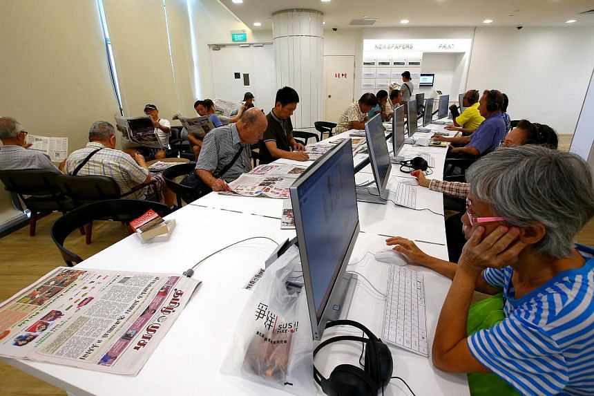 People reading newspapers and surfing the Internet in the new Yishun Public Library. NLB will partner with IMDA to extend the reach of digital training to more than 300,000 Singaporeans over five years.