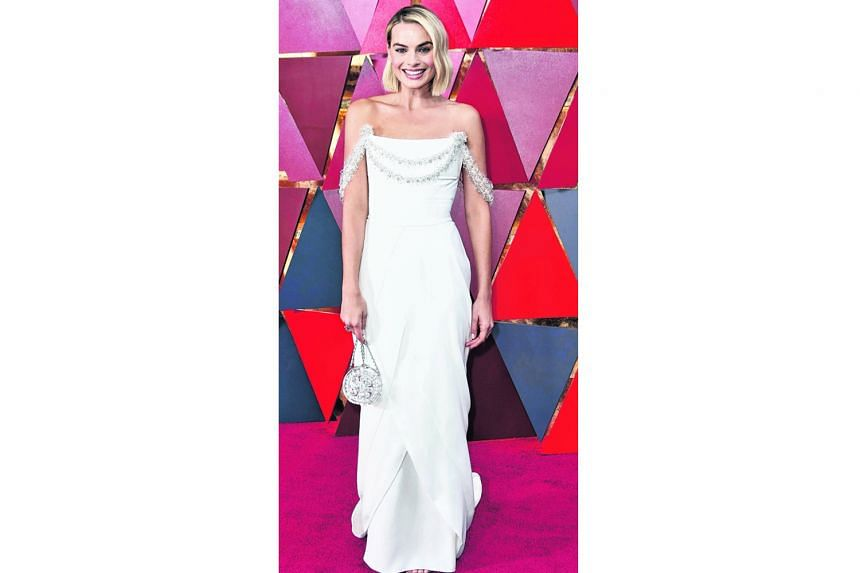 Margot Robbie, star of I, Tonya, looks like a tall drink of water in this chic white number by Chanel Haute Couture - designed exclusively for her by Karl Lagerfeld. It has just the right amount of sparkle, and when combined with her simple styling, the A