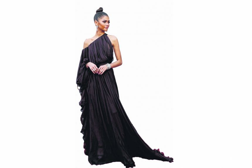 The Greatest Showman star Zendaya is positively regal in a draped Giambattista Valli Couture chiffon goddess gown. The deep chocolate brown colour looks beautiful against her caramel skin and the unusual asymmetrical sleeves give the dress an interesting