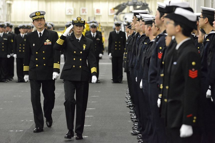 Newly-appointed Commander of First Escort Division of the Japan Maritime Self-Defense Force, Ryoko Azuma (second from left), salutes soldiers on the helicopter carrier Izumo at a port in Yokohama, Japan, on March 6, 2018.