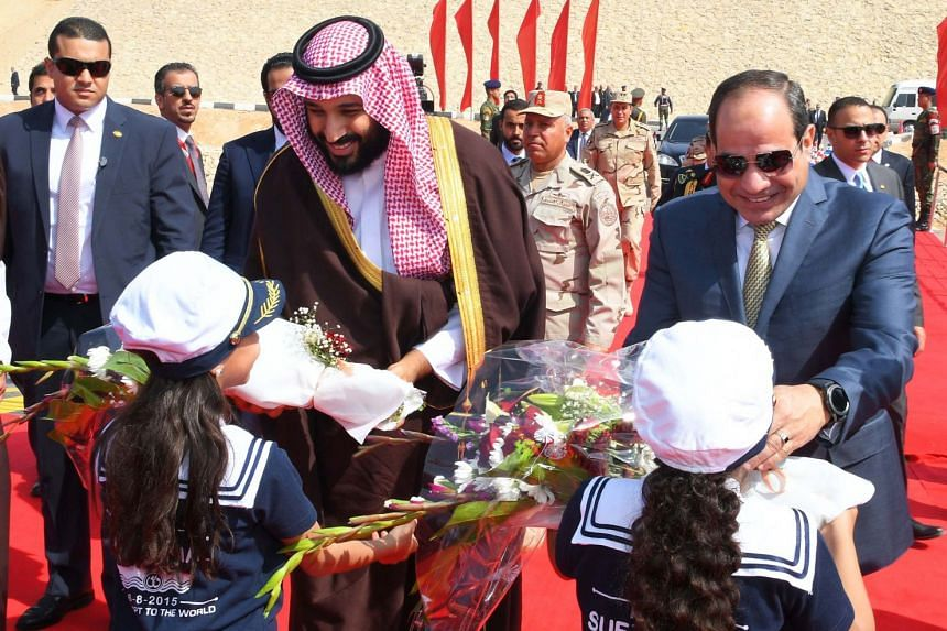 Egyptian President Abdel Fattah al-Sisi and Saudi Arabia's Crown Prince Mohammed bin Salman receive flowers as they visit the Suez Canal on March 5, 2018.